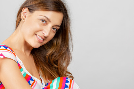 Portrait of a beautiful, cheerful young woman on a gray background. Female face close up