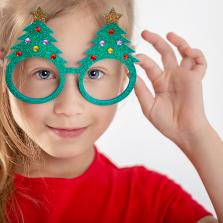 Portrait of a beautiful little girl with glasses. Christmas accessory. Face close up Фото со стока