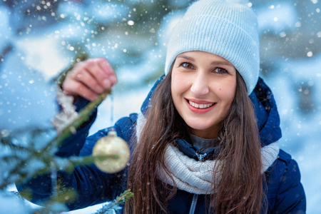 Portrait of a beautiful happy woman in winter outdoors. Girl decorates the christmas tree Imagens