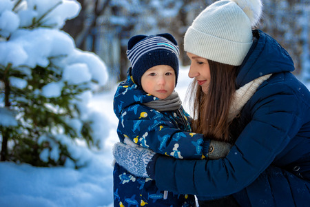 Woman and child in winter in nature. Portrait of a happy family