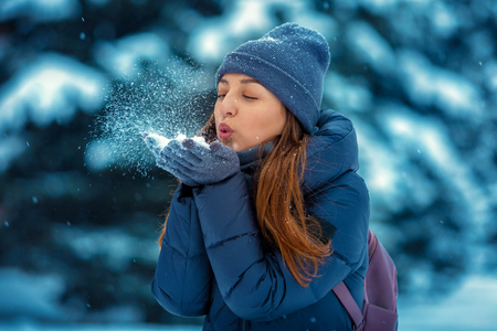 Portrait of a beautiful young woman in winter in nature