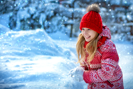 Portrait of a cheerful child in the winter outdoors. Girl laughs