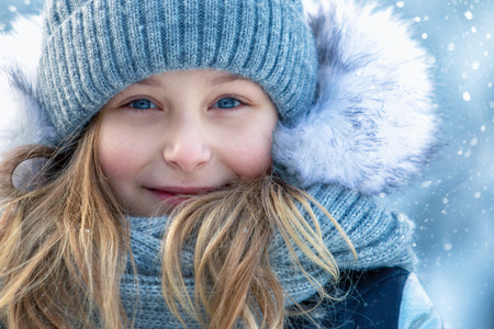 Portrait of a beautiful smiling girl in winter outdoors. Face close up