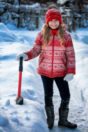 Portrait of a happy child in the winter. Cheerful girl outdoors