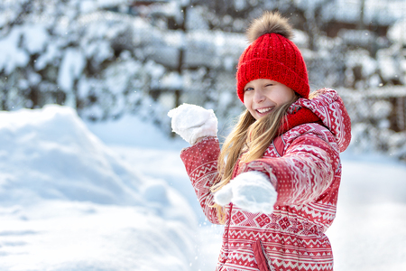 Portrait of a happy child in the winter. Cheerful girl outdoors. Snowball game