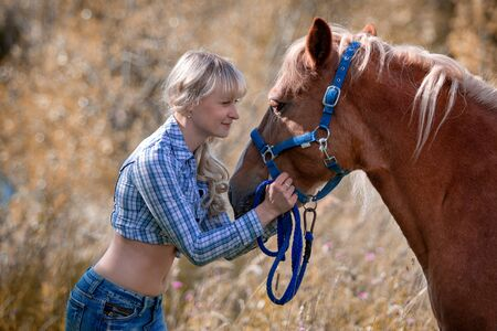 Portrait of a beautiful young cheerful woman with a horse outdoors Imagens