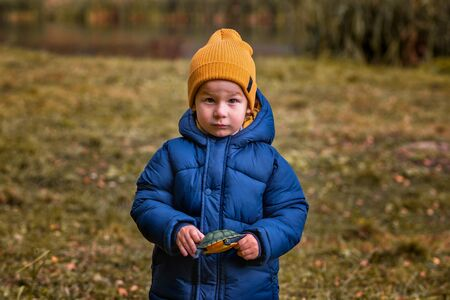 Portrait of a child outdoors. Serious boy with a toy in his hands