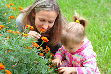 Happy Mom and daughter sniffing flowers in the garden