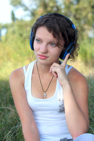 A young girl listens to music on the nature