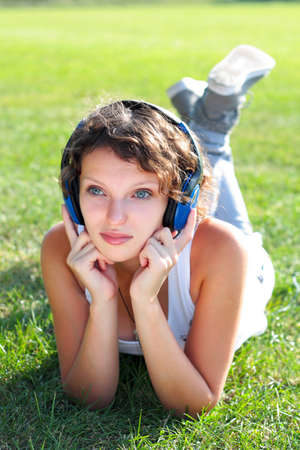 young girl listens to music on naure