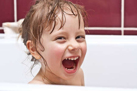 Cute two-year-old girl looking out of a bath and smiling photo