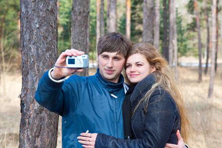 happy smiling couple taking photo with camera photo