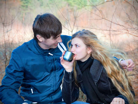 Happy couple drinking tea outside in forest photo