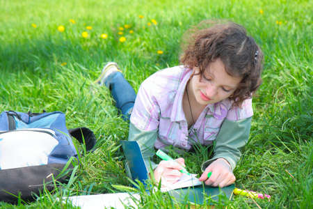 Girl student in park writes in writing book