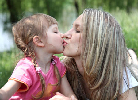 Little girl kissing her mother in a park photo