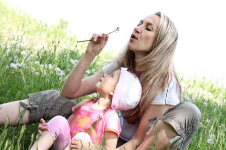 Mother and Daughter Blowing Dandelion Seeds Together photo