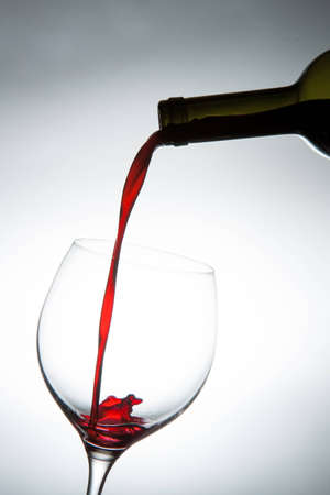 Pouring red wine into a glass. photo
