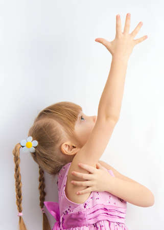 a little girl reaching for something with his hands.