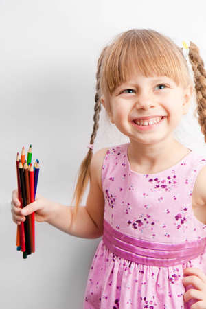 pigtail: Little girl holding a pencil and smiles. Stock Photo