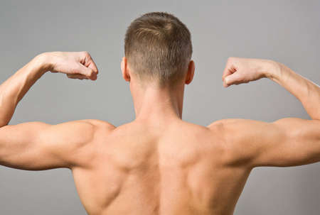 Back of sexy muscular man on a gray background