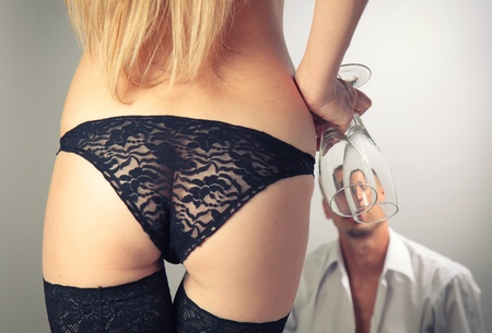 Beautiful sexy girl came with glasses of champagne to the man.