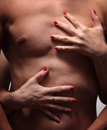 Beautiful female hands embrace a muscular male torso Stock Photo
