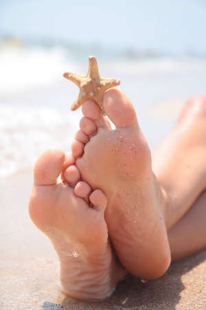 beach feet: A wet female feet on the beach and sand Stock Photo