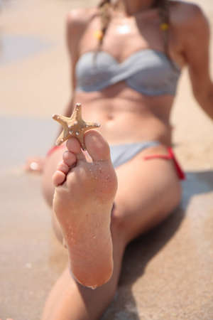 girl soles: A wet female feet on the beach and sand Stock Photo