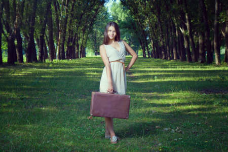 Girl with a suitcase in the park. Stock Photo
