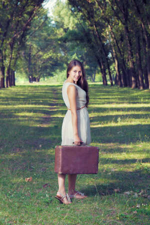 Girl with a suitcase goes on a dirt road Stock Photo