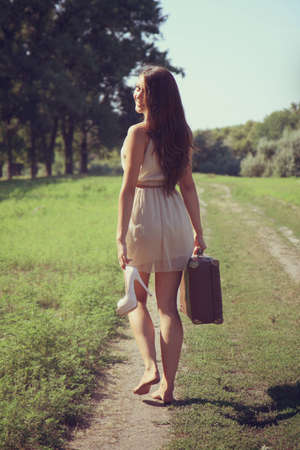 Girl with a suitcase goes barefoot on a dirt road Stock Photo