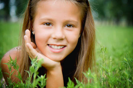 girl face close up: Portrait of a smiling girl on the grass