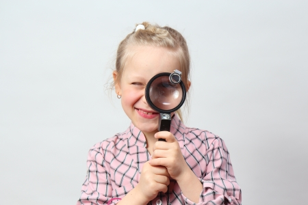 Funny girl explores with a magnifying glass  Stock Photo - 18713629