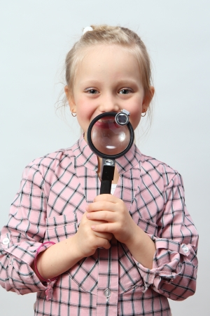 explores: Funny girl explores with a magnifying glass  Stock Photo