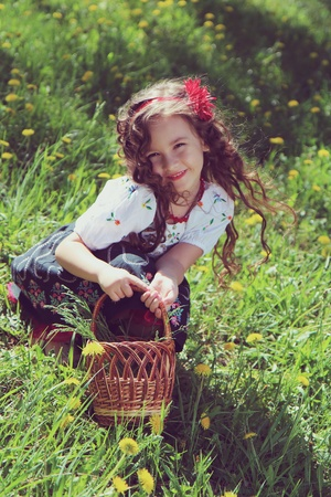 Little girl in the Ukrainian national costume on grass.