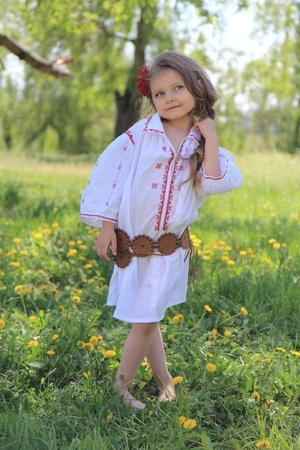 national costume: Little girl in the Ukrainian national costume on grass.
