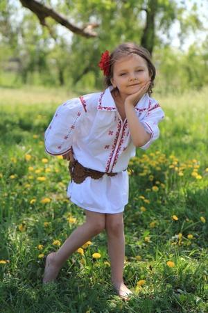 Little girl in the Ukrainian national costume on grass.