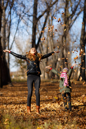 Young mother and her toddler girl in autumn park Stock Photo