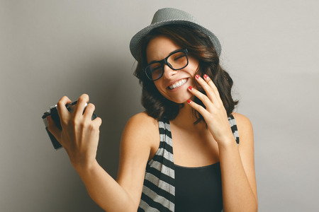 Beautiful, naturall girl in a hat with camera. Stock Photo