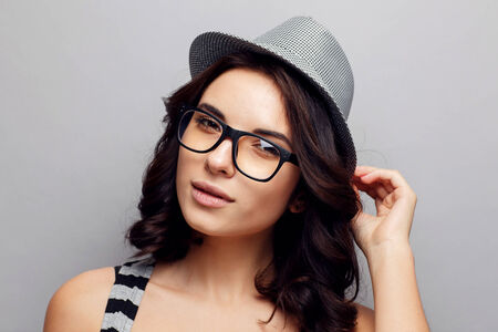 Beautiful attractive girl in a hat and glasses. Stock Photo