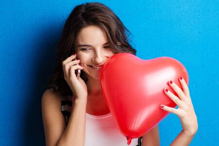 Love and valentines day woman holding heart smiling cute and adorable on blue background. Beautiful caucasian woman in love.