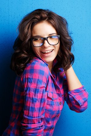 Portrait woman in glasses  on blue background.