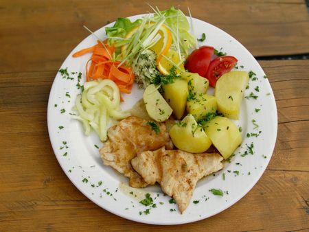 chicken steak with boiled potatoes and vegetables on white plate photo