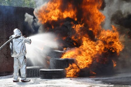 hellfire: firefighter  quenches  a burning tyres