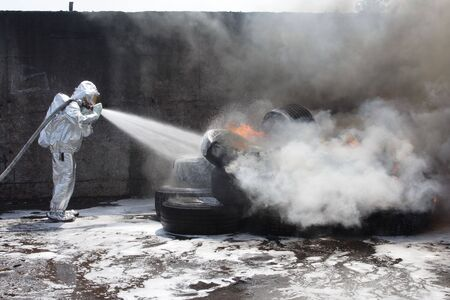 firefighter  quenches  a burning tyres