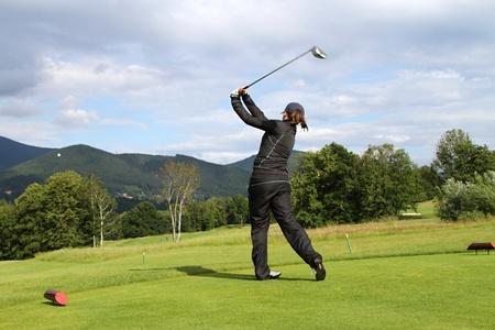 young Girl playing golf -  shooting a golf ball photo