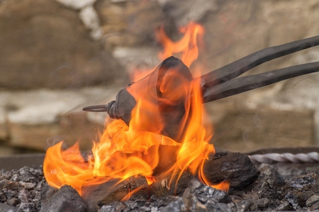 smithery: Blacksmith heating up a making small iron bell
