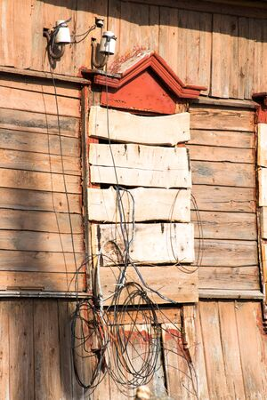 without windows: Boarded up window of the old farmhouse with dangling wires Stock Photo