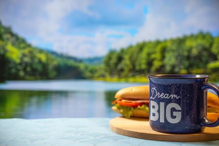 mug of hot coffee on the background of a beautiful mirror lake at sunrise. Morning at the camp. Traveling in a nature park. Tea Cup On Table By Mountain Against Sky