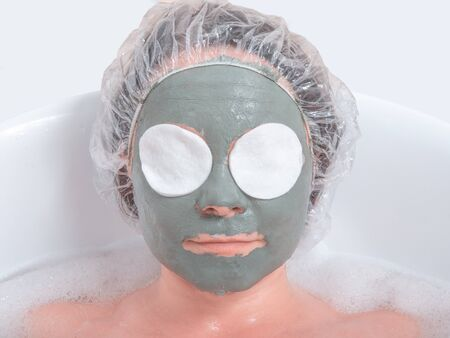 Portrait of a woman in facial mud mask lying in the bath. Face Skin care Archivio Fotografico